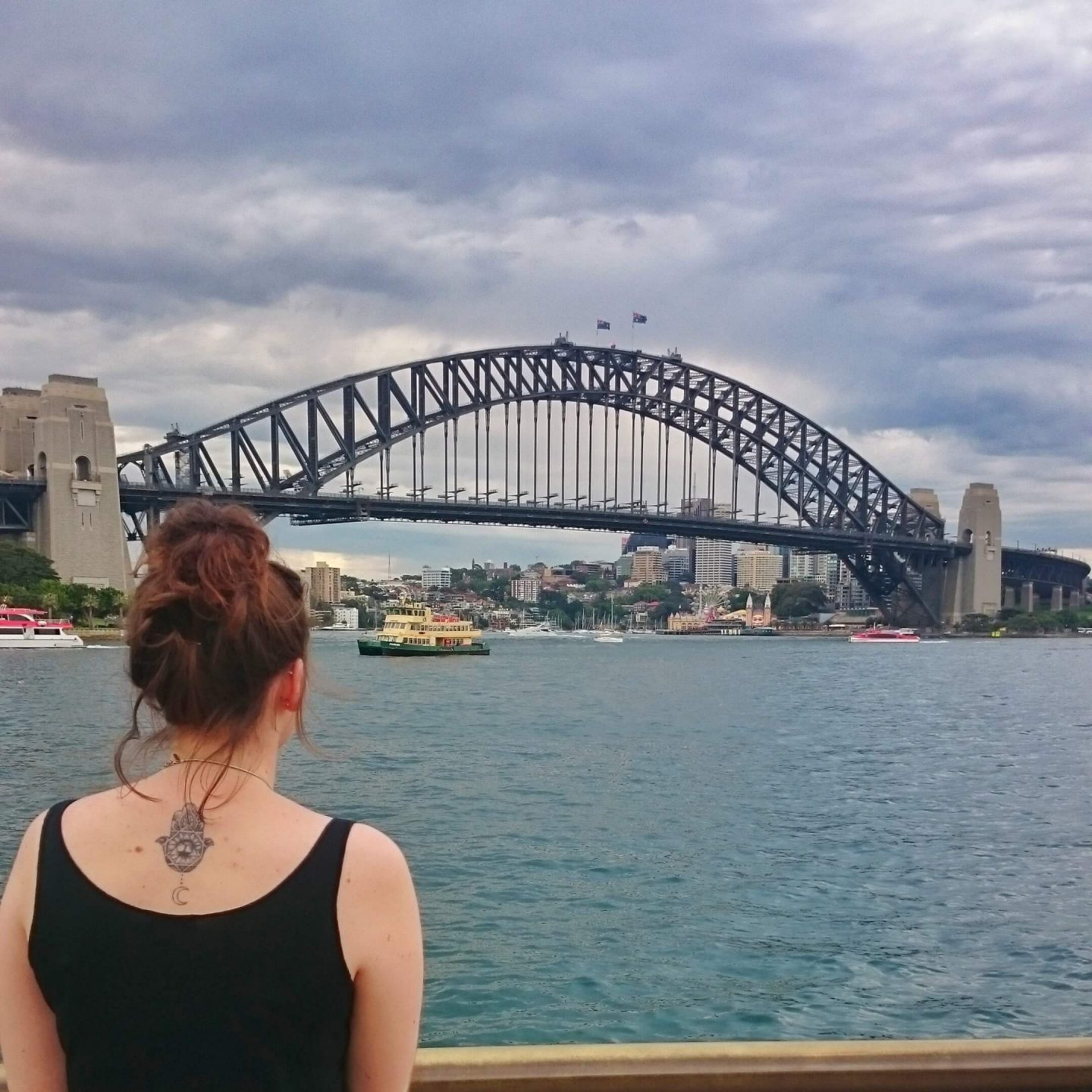 young-woman-looking-across-sydney-harbour-at-sydney-harbour-bridge
