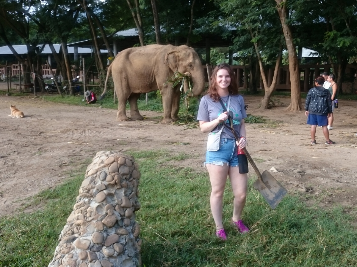 Young woman stood in front of elephant.