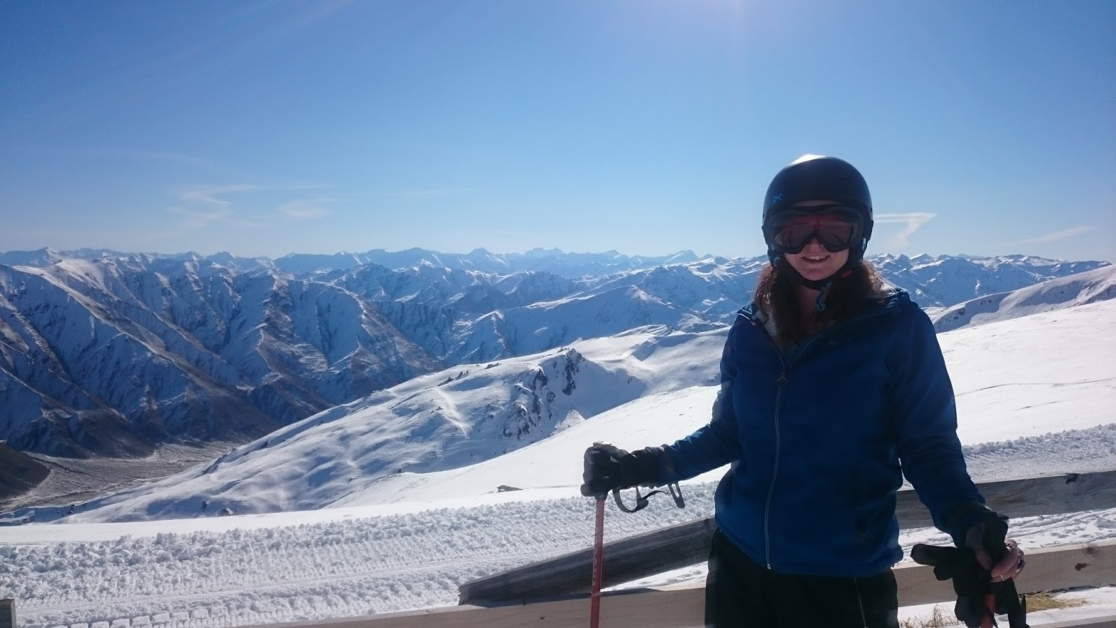 young-woman-in-skiing-gear-with-snowy-mountain-views-behind