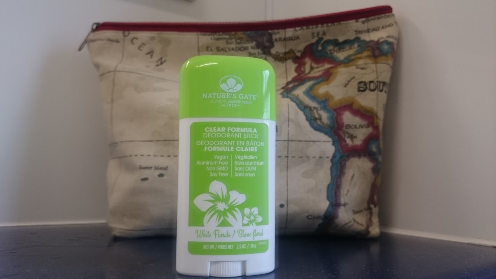 green-and-white-bottle-of-natures-gate-deodorant-with-washbag-in-background
