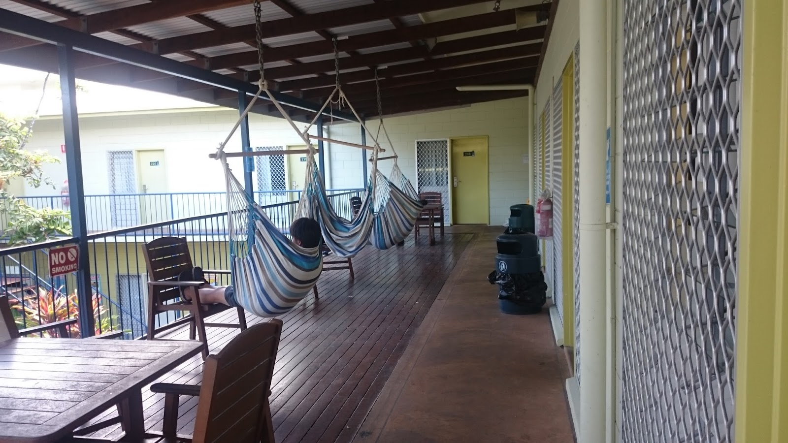 people-sitting-in-hammocks-on-balcony-at-yha-cairns-central-hostel