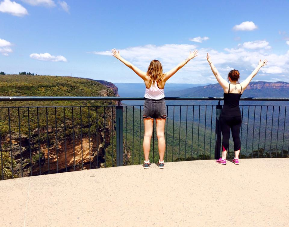 two-women-with-arms-in-the-air-looking-out-over-blue-mountains-sydney-australia