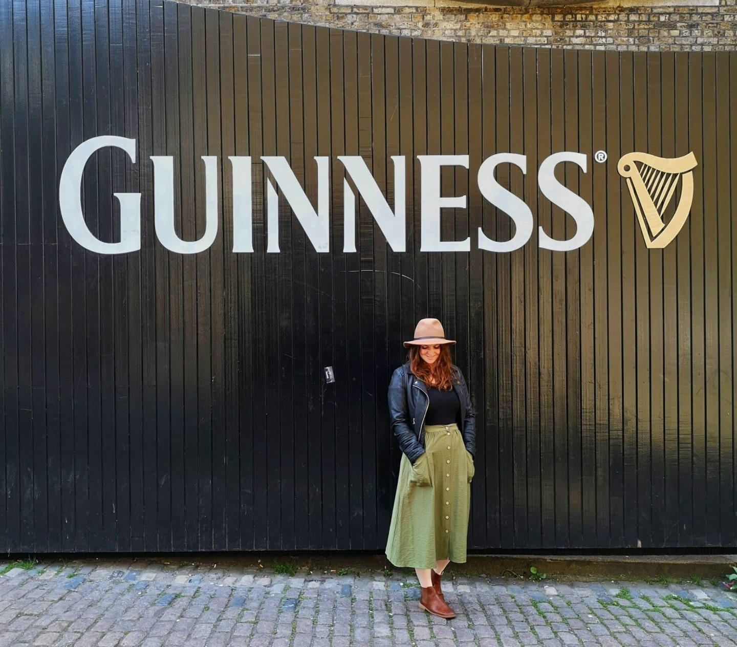 Young woman in hat stood outside gates of Guinness Storehouse, Dublin.