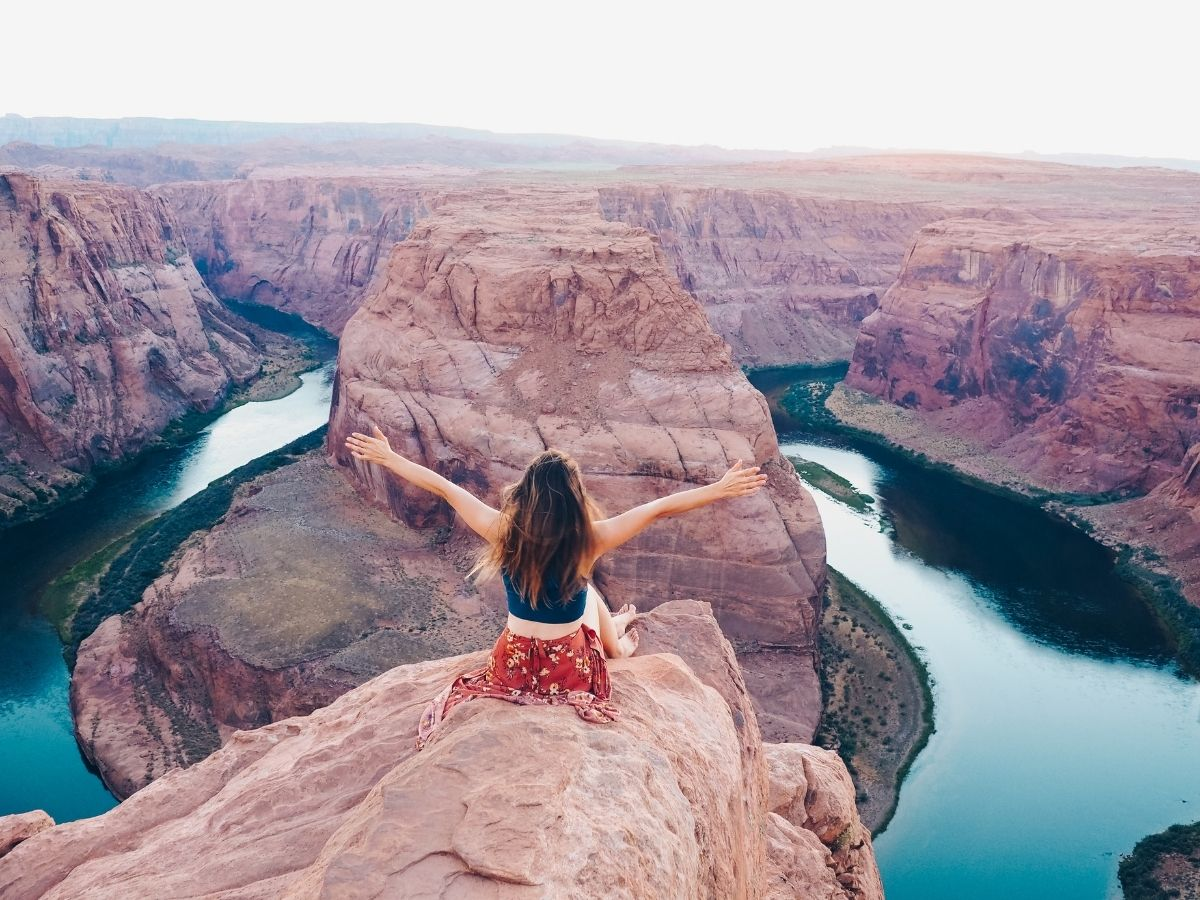 Young girl sitting on cliff facing over canyon